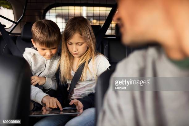 Sibling using digital tablet while sitting in car with father in foreground
