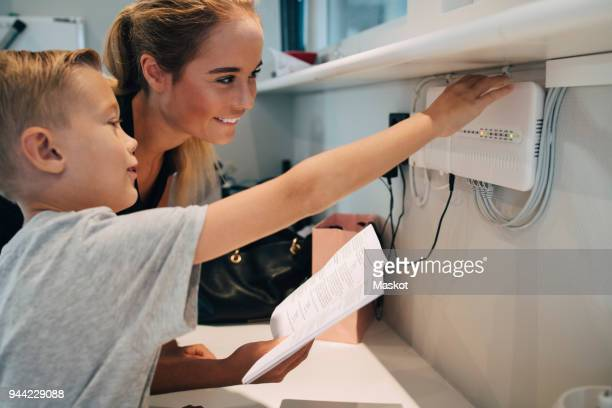 Siblings adjusting household equipment with instruction manual at home