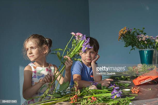 Siblings arranging flowers at table