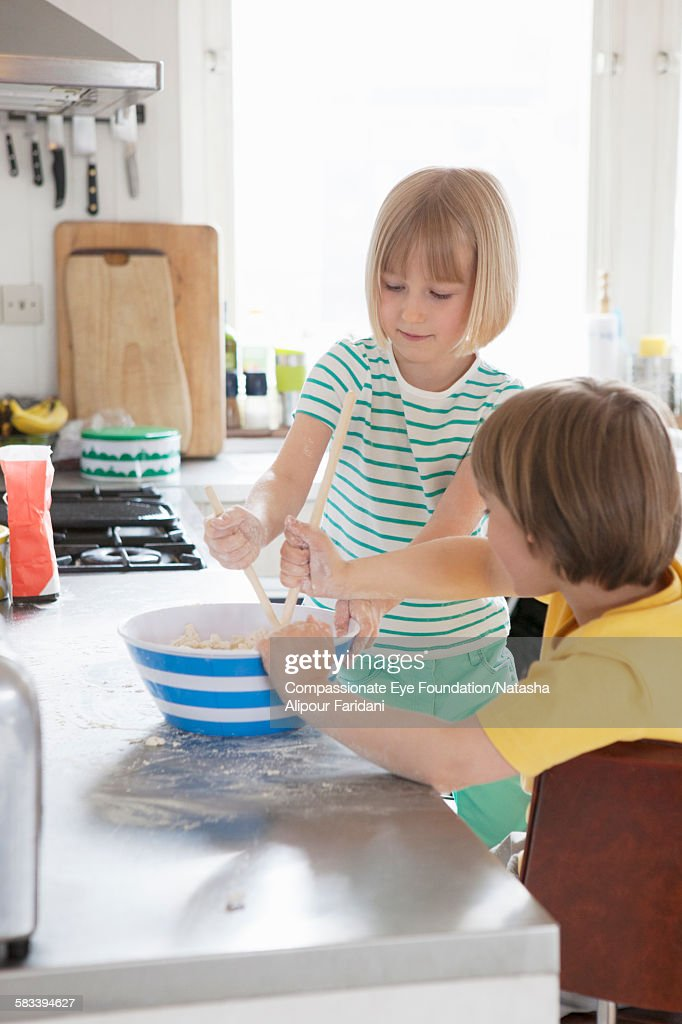 Siblings baking in kitchen : Stock Photo