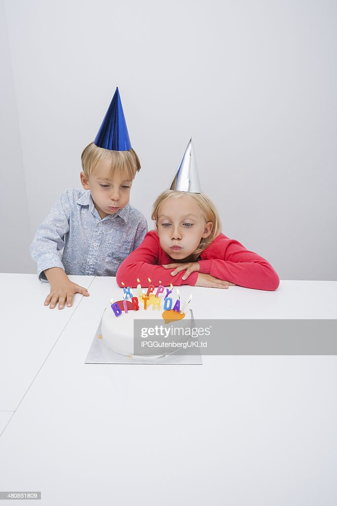 Siblings blowing birthday candles at table in house : Stock Photo