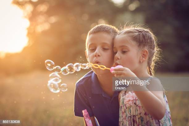 siblings blowing bubbles from bubble wand - life events stock pictures, royalty-free photos & images