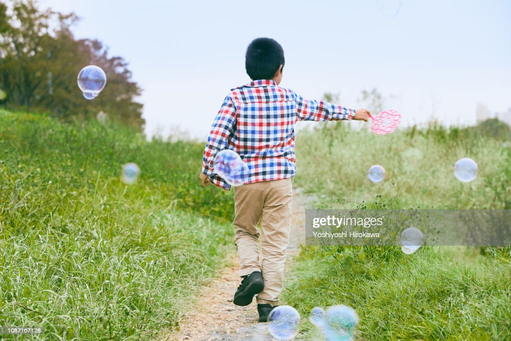 Siblings blowing bubbles river bank togather. : Stock Photo