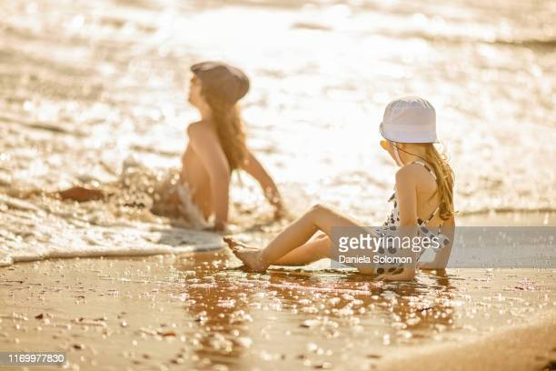 siblings boy and girl playing on the beach - arab feet photos et images de collection