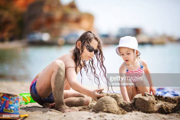 siblings boy and girl playing on the beach - 2 kid in a sandbox stock photos and pictures