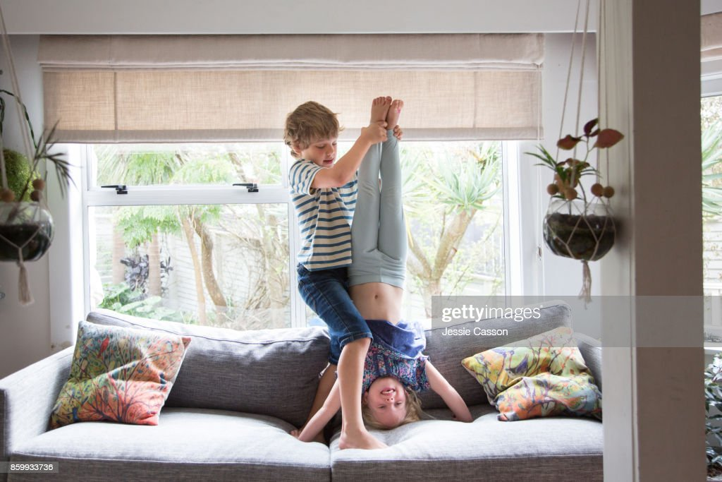Siblings - brother helping and supporting sister to do a headstand : Stock Photo