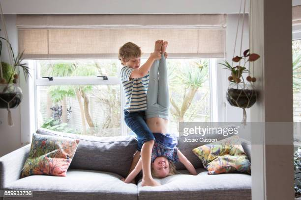 siblings - brother helping and supporting sister to do a headstand - zus stockfoto's en -beelden