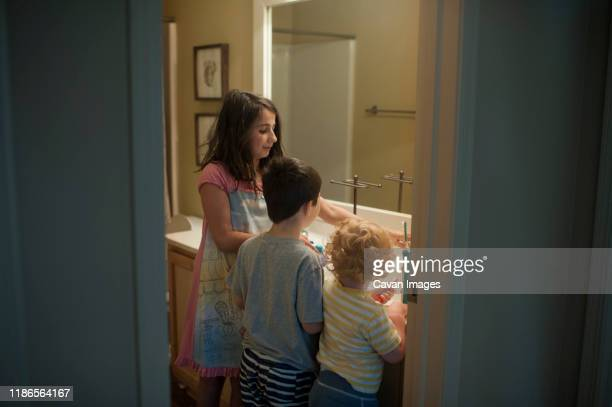 siblings brushing teeth in bathroom seen through doorway at home - sister stock pictures, royalty-free photos & images