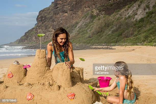 Siblings building sandcastle on vacation to a tropical destinati