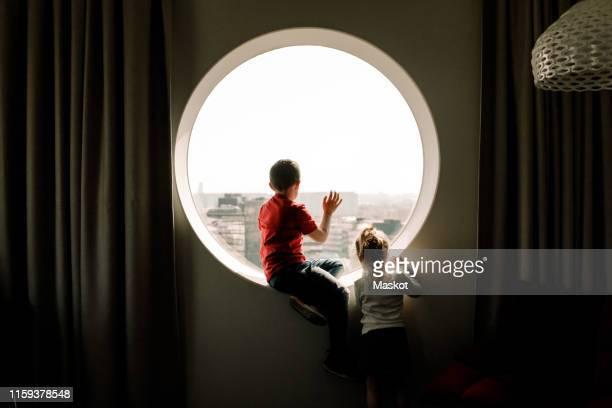 siblings by window in hotel room - círculo imagens e fotografias de stock
