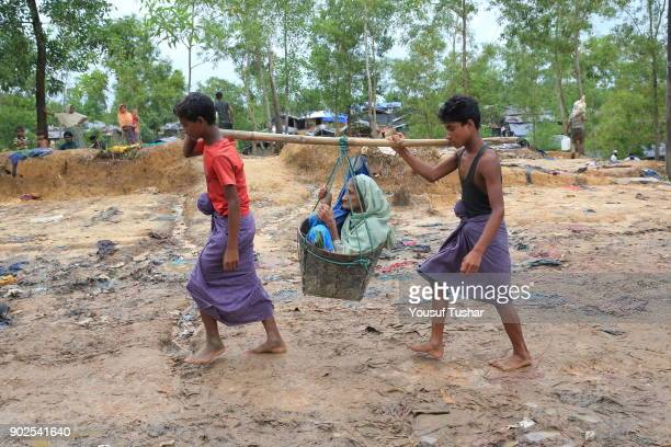 Siblings carry their mother at Palongkhali in Coxs bazar Bangladesh Thousands of Rohingyas still crossing the border between Myanmar and Bangladesh...