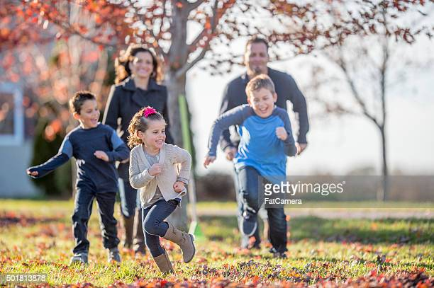 siblings chasing each other through the yard - kids playing tag stock photos and pictures
