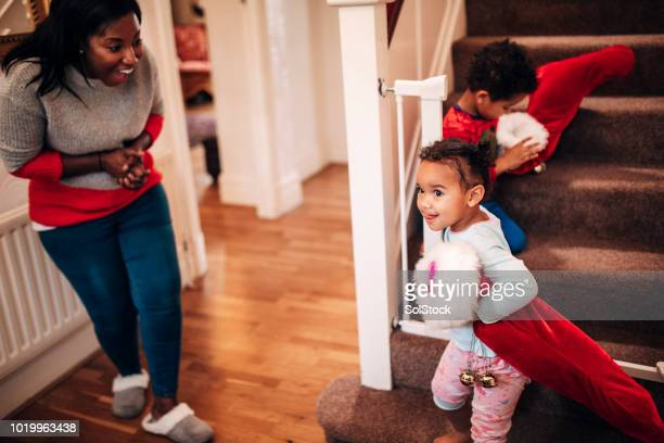 siblings coming down the stairs on christmas morning - black stockings stock pictures, royalty-free photos & images