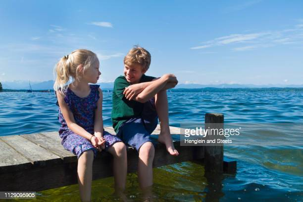siblings cooling feet in water, lake starnberg, bavaria, germany - mujeres fotos stock pictures, royalty-free photos & images