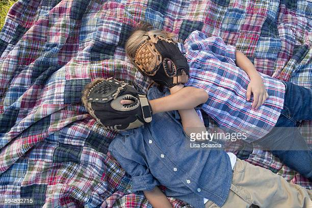 Siblings covering face with baseball gloves while resting on blanket