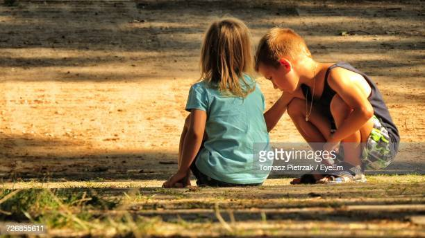 Siblings Crouching While Playing At Field