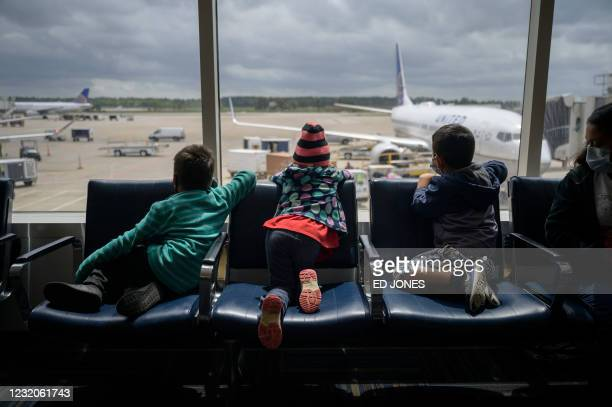 Siblings Dariel ]and Diana from Honduras sit with Daniel from El Salvador at Houston airport during a translfer on March 30, 2021 after being...