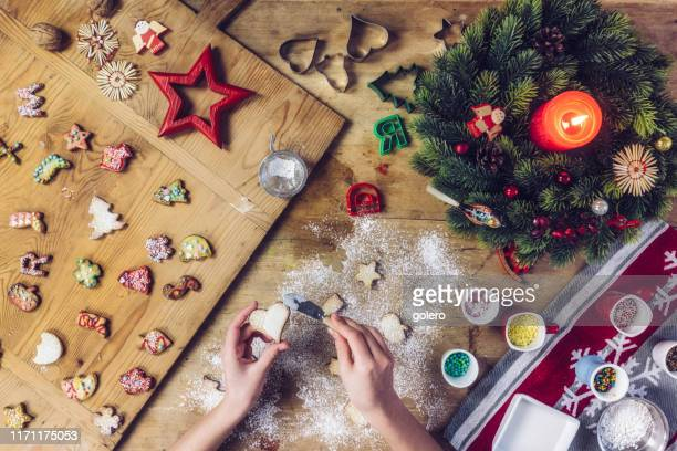 siblings decorating christmas cookies together at wooden table - fotosession stock photos and pictures