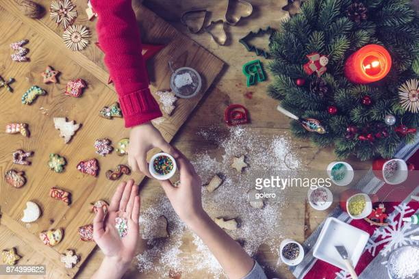 siblings decorating christmas cookies together - fotosession stock photos and pictures