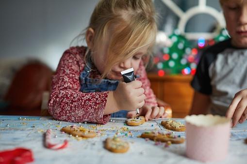 Siblings decorating gingerbread men - gettyimageskorea