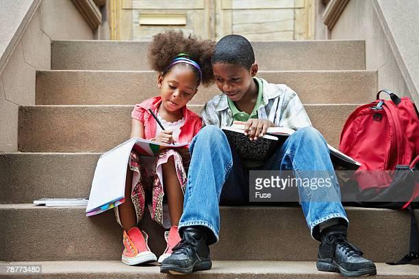 Siblings Doing Homework on Stairs