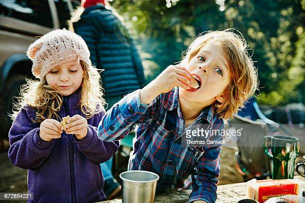 Siblings eating graham crackers while camping