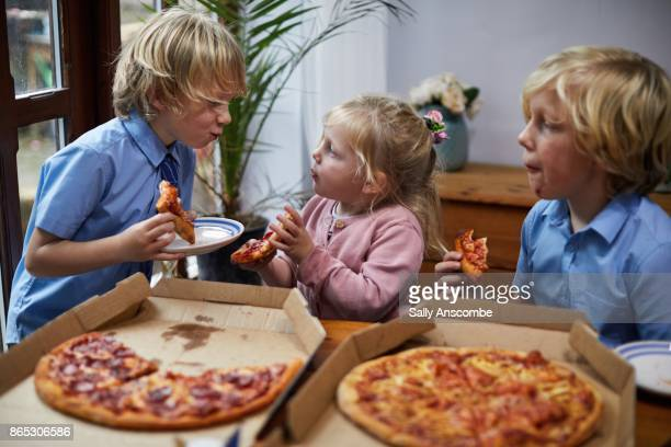 siblings eating pizza together - take away food stock pictures, royalty-free photos & images