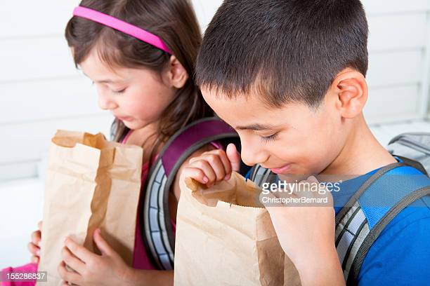 siblings eating school lunch - lunch bag stock pictures, royalty-free photos & images