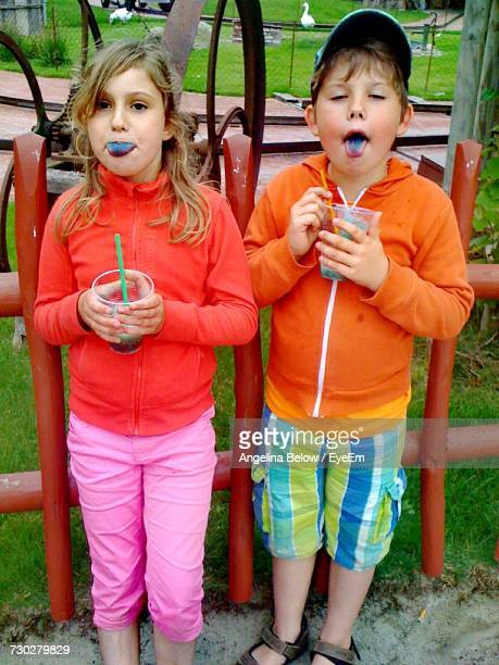Siblings Eating Shaved Ice While Standing At Park