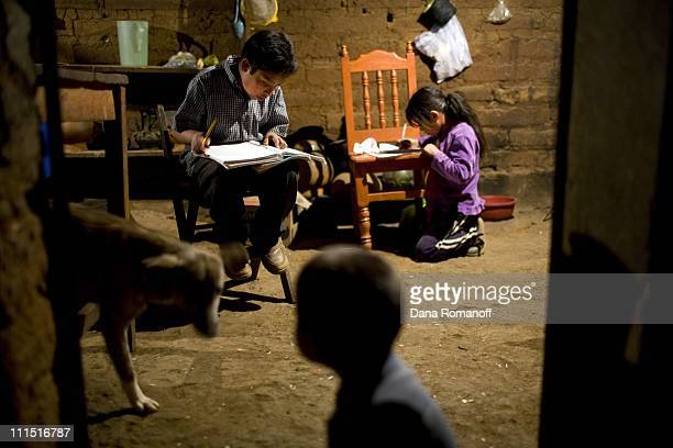 Siblings Eberh and Sara Gaspar Morales do homework in the kitchen of their two room earthen home on February 28 2008 in the small mountainous town of...