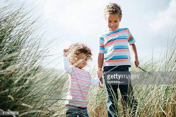 Geschwister Genießen Sie einen Spaziergang durch die Wiese