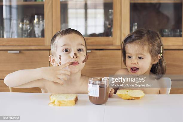 Siblings enjoying chocolate spread and toast for snacks