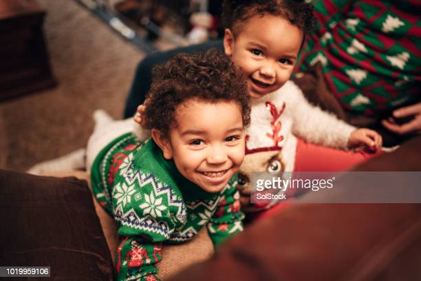 siblings enjoying christmas day - christmas jumper stock photos and pictures
