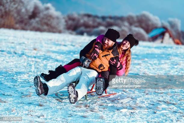 一緒にそりに下り坂の雪の転倒を楽しむ兄弟 - ボブスレーをする ストックフォトと画像