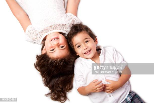 Siblings Enjoying On Bed Against White Background