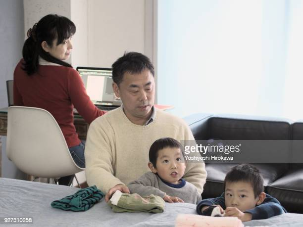 Siblings folding laundry with father