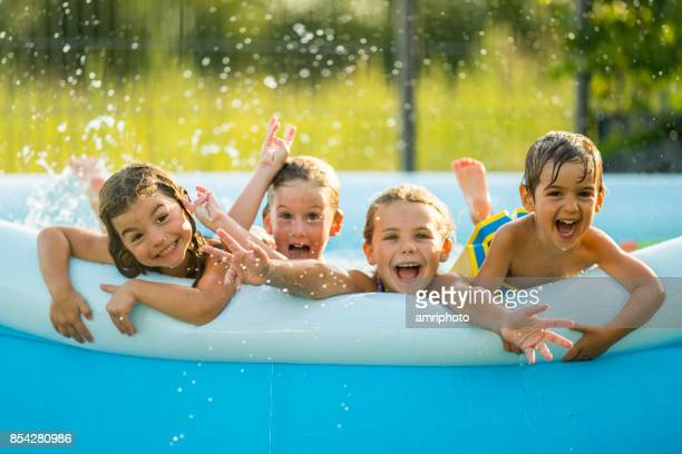 siblings - four happy young kids in swimming pool - heat wave stock pictures, royalty-free photos & images