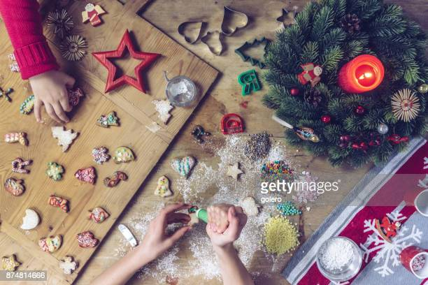 siblings hands decorating christmas cookies together - fotosession stock photos and pictures