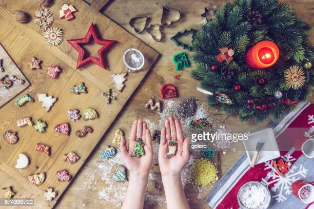 siblings hands holding christmas cookies over wooden table - fotosession stock photos and pictures