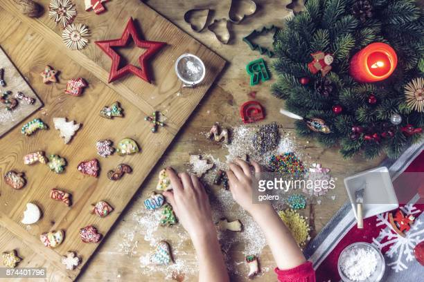 siblings hands taking christmas cookies from wooden table - fotosession stock photos and pictures