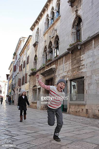 Siblings happily roaming old town in Porec