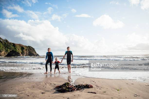 siblings having fun together - beach stock pictures, royalty-free photos & images