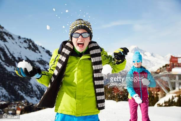 Siblings having snowball fight