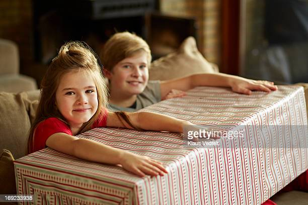 Siblings holding on to big present