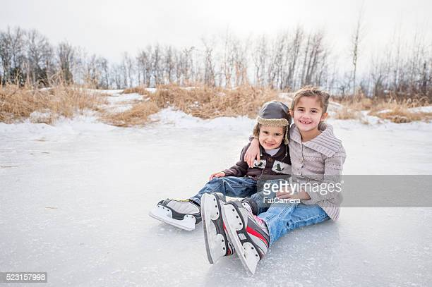 Siblings Ice Skating Outside
