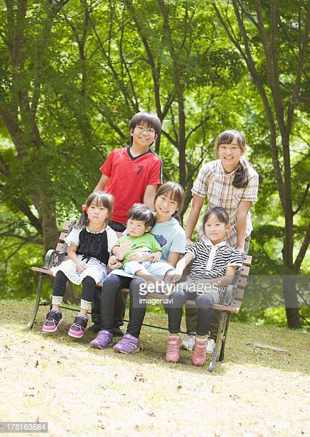 Siblings in a big family sitting on a bench