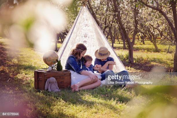Siblings in An Orchard with Lace Teepee Looking away from Camera