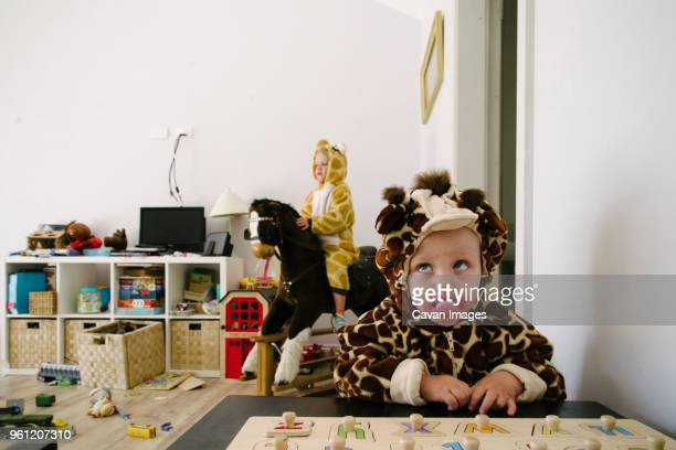 siblings in animal costumes playing at home - chaos stock-fotos und bilder