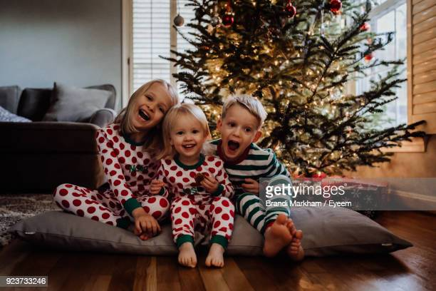 siblings in costume sitting against christmas tree at home - baby human age stock pictures, royalty-free photos & images