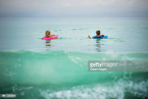 siblings in inflatable rings floating on sea - anna maria island stock pictures, royalty-free photos & images